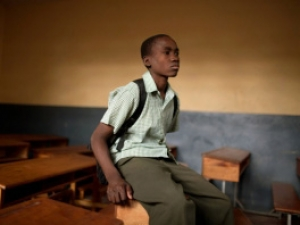 A kid sitting in an empty classroom